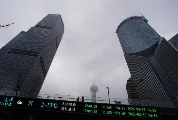 People are seen on a pedestrian overpass with an electronic board showing the Shanghai and Shenzhen stock indexes, following an outbreak of the novel coronavirus in the country, at Lujiazui financial district in Shanghai, China